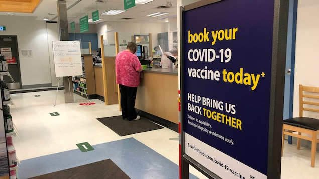Un panneau devant le comptoir d'une pharmacie invite à prendre rendez-vous pour se faire vacciner.