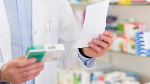 Les mains d'un pharmacien tenant une prescription et des médicaments.