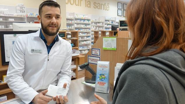 Un pharmacien derrière un comptoir de services répond à une cliente.