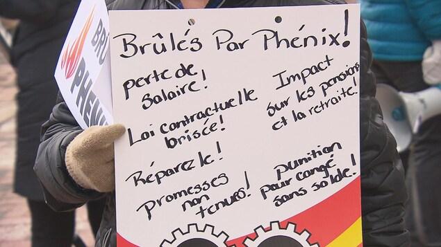 Pancarte d'un manifestant mécontent du système de paye Phénix.