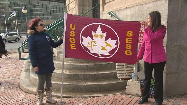 Travailleuses du Syndicat des employé-e-s de la Sécurité et de la Justice avec un drapeau de leur organisation syndicale.