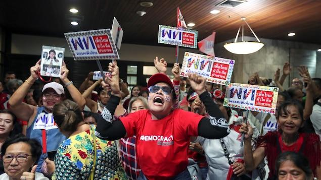 Une femme semble crier victoire, encerclée par d'autres militants qui brandissent des pancartes en faveur du parti.