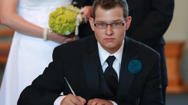 Philip Chicoine signe un document lors du mariage de son frère.