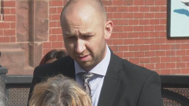 Philip Hutching discute avec d'autres personnes dehors près du palais de justice.