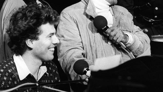 Photo en noir et blanc et de profil de Philippe Chatel, qui sourit à quelqu'un hors champ. Il y a un micro devant lui.