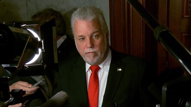 Le premier ministre du Québec Philippe Couillard debout dans le couloir de l'Assemblée nationale, répond aux questions relativement à la Commission sur le racisme et la discrimination systémique