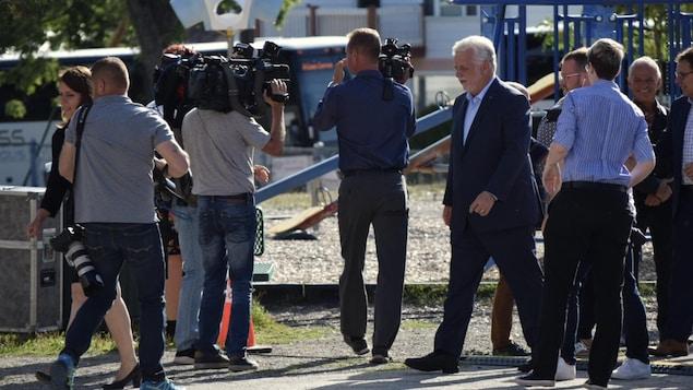 Philippe Couillard sur le terrain d'une école avec des journalistes
