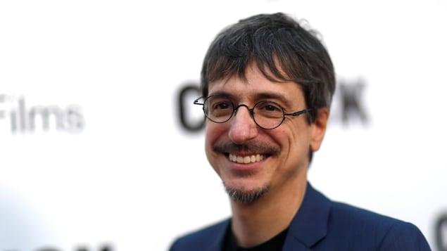 Un homme vêtu d'un veston prend la pose devant des caméras.