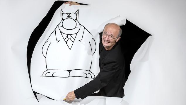Le dessinateur découpe son personnage dessiné sur un papier.