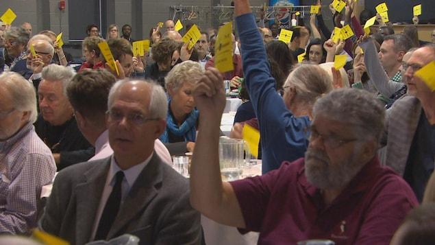 Des membres de la SFM votent à main levée lors de l'assemblée générale annuelle de l'organisme. Au premier plan : Philippe Mailhot (à g.) et Léo Robert
