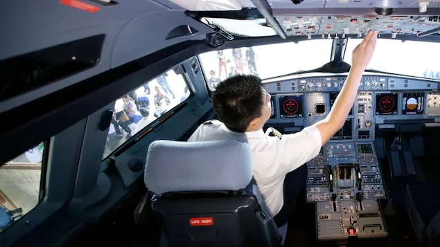 a pilot reaches for the cockpit controls. A B.C. woman claims her airline pilot husband flew their daughter to China, where they both remain.