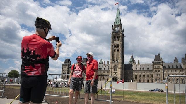 Un homme prend une photo de deux personnes devant l'édifice du Centre.