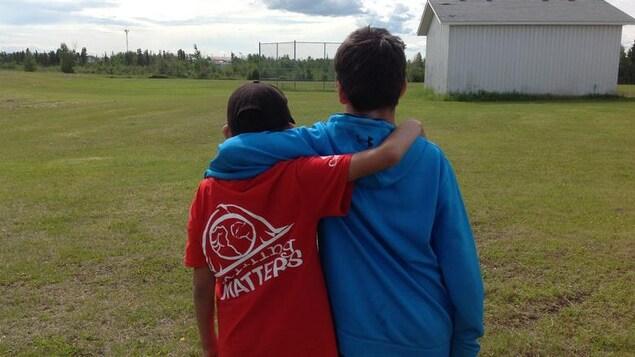 Deux jeunes regardent un terrain de sport