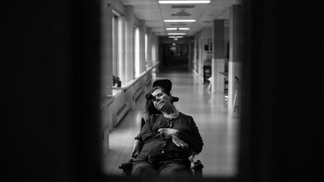 Jamie Woytiuk a photographié sa mère dans son fauteuil roulant, la tête tombant du côté gauche. Derrière elle, il y a un long corridor.