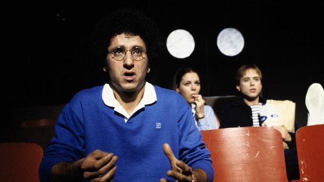 Les trois comédiens sont assis dans différentes rangées d'une salle de cinéma.