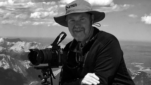 Homme avec une caméra devant un paysage de montagnes.