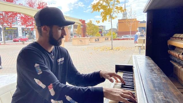 Un jeune homme joue du piano.