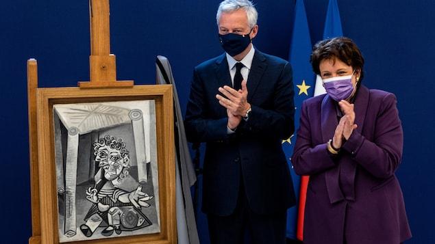 L'homme et la femme sont à côté d'une petite peinture en noir et blanc et applaudissent.
