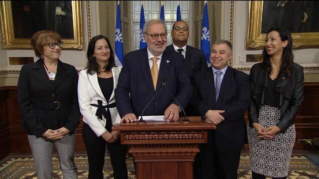 Pierre Arcand devant un lutrin, entouré des députés libéraux Hélène David, Marie Montpetit, Sébastien Proulx, Marwah Rizqy et Saul Polo.