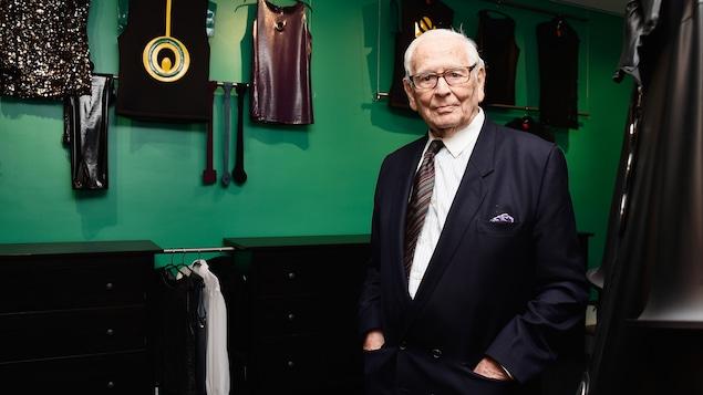 Un homme habillé d'un complet cravate pose devant un mur où des vêtements griffés sont accrochés.