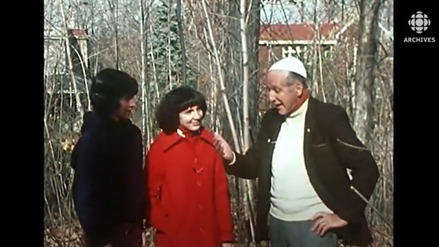 Homme qui parle avec des jeunes en forêt.