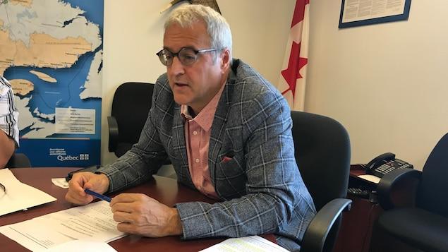 Pierre Dufour parle aux journalistes réunis autour d'une table de conférence.
