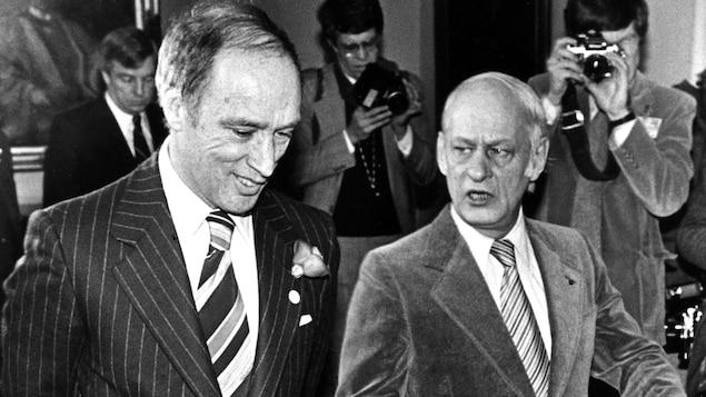Le premier ministre du Canada Pierre Elliott Trudeau écoute en souriant son homologue du Québec, René Lévesque, qui lui parle avec une mine préoccupée.