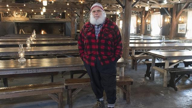 Pierre Faucher pose debout dans la salle à manger de sa cabane à sucre.
