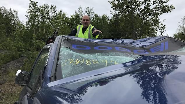 Pierre Girard examine un véhicule accidenté.