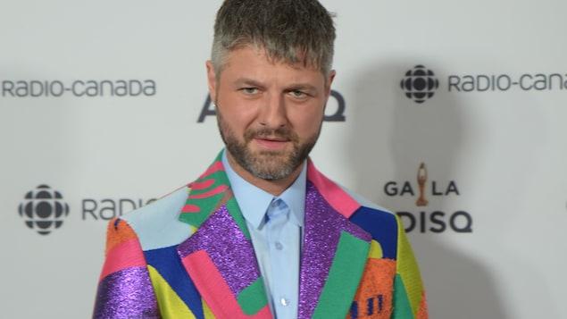 Le chanteur est vêtu d'un veston de couleurs différentes.