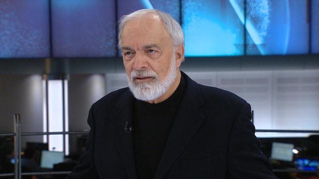 Un homme ayant une barbe blanche regarde devant lui, la bouche légèrement ouverte. Il porte un veston noir et un chandail noir.