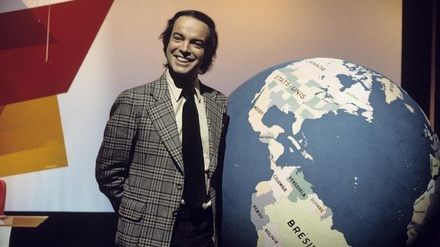 Dans un studio de télévision, Pierre Nadeau est debout, souriant, devant un gros globe terrestre.