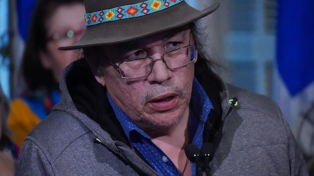 Le visage de l'homme avec des drapeaux du Québec dans le fond.