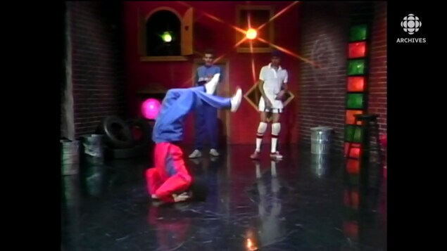 Pierre Perpall fils exécute un mouvement de chandelle en dansant. Ses deux partenaires de breakdance regardent en arrière-plan.