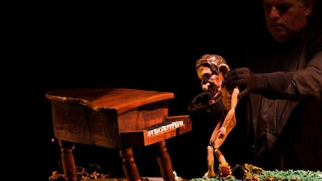 Pierre Robitaille à l'oeuvre lors du spectacle Cabaret Gainsbourg. Le marionnettiste manipule un petit Serge Gainsbourg qui joue du piano.