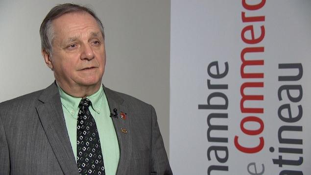 Pierre Samson en entrevue devant une bannière comportant le logo de l'organisme.