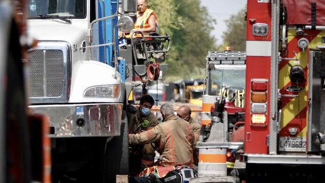 Des pompiers travaillent à dégager une personne sous un camion.