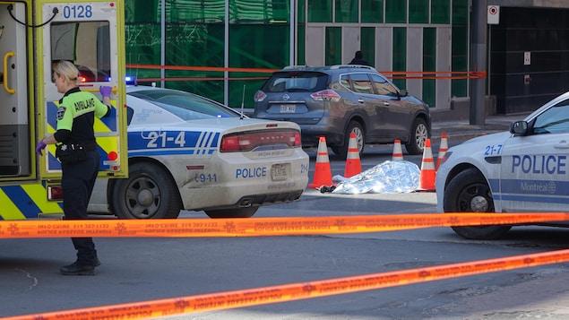 Une couverture argentée recouvre le corps de la victime qui est entouré de voitures de police.