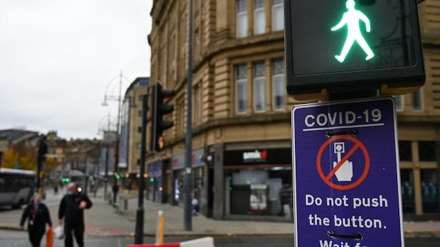 Des piétons à Bradford passent devant un panneau de feux de circulation, qui leur conseille de ne pas utiliser le bouton à cause de la COVID-19.