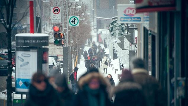 Piétons sur la rue Sainte-Catherine de Montréal, près de la Place des Arts, en hiver