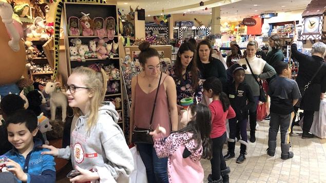 Les enfants et des bénévoles font la file au magasin Banjo, dans Saint-Roch.