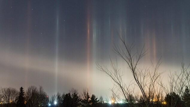 Colonnes lumineuses verticales dans le ciel.