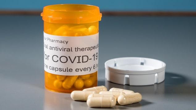 Flacon d'ordonnance et capsules illustrant des essais de traitement antiviral oral contre le virus SRAS-CoV-2.