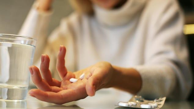 Une femme tient des cachets dans sa main.