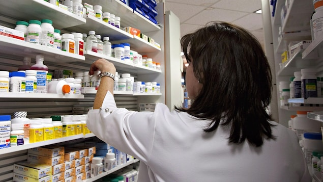Une technicienne ramasse une bouteille de pilules sur une des étagères d'une pharmacie.