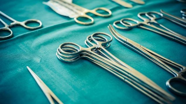 Des pinces chirurgicales sont étalées sur un tissu stérile.