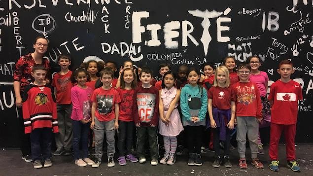 Des élèves d'une classe de deuxième année avec des chandails rouges posent en groupe devant un mur noir avec des écritures en blanc.