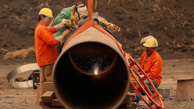 Trois travailleurs s'affairent sur une canalisation.