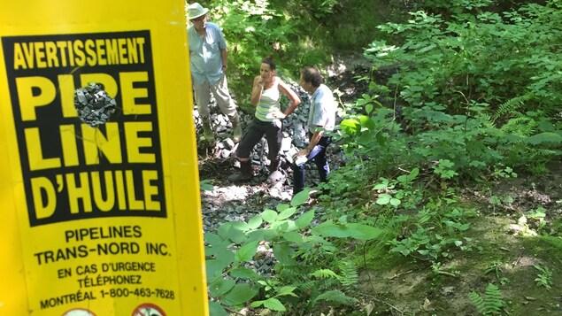 Sylvie Rozon et Guy Coderre se tiennent derrière une affiche jaune qui indique la présence d'un pipeline de Trans-Nord inc. dans un boisé de Saint-Lazare.