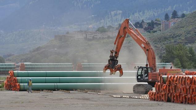 Une chargeuse est utilisée pour déplacer les sections d'oléoduc.